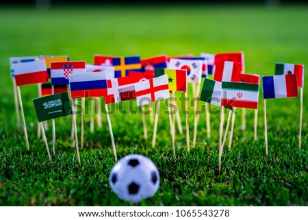 Football ball on green grass and all national flags #1065543278