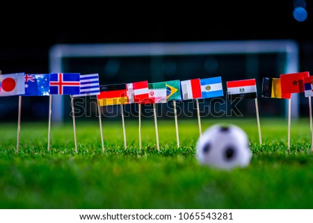 Football ball on green grass and all national flags  #1065543281