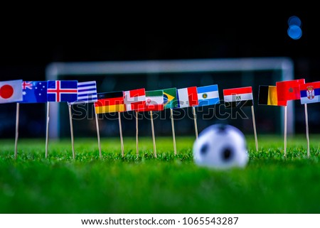 Football ball on green grass and all national flags  #1065543287