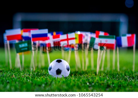 Football ball on green grass and all national flags of FIFA World Cup, Russia 2018. #1065543254