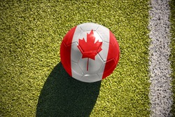 football ball with the national flag of canada lies on the green field near the white line