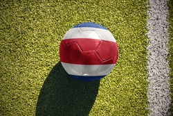 football ball with the national flag of costa rica lies on the green field near the white line