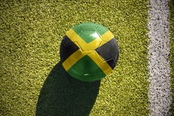 football ball with the national flag of jamaica lies on the green field near the white line