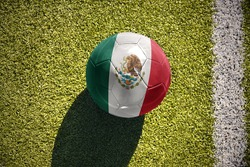 football ball with the national flag of mexico lies on the green field near the white line