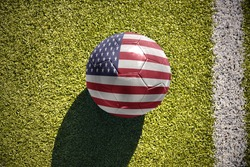 football ball with the national flag of united states of america lies on the green field near the white line