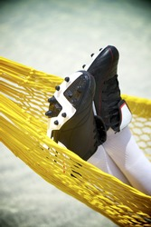 Football boots close-up of soccer player relaxing in beach hammock