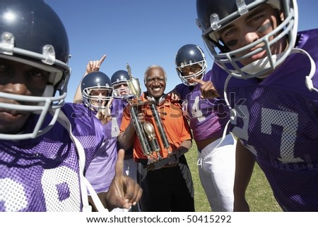 Football Coach and Players holding trophy on field, portrait, (portrait)