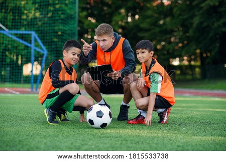 Football coach instruct teen football players. Young professional coach explains for kids the strategy of the game. Stock fotó ©