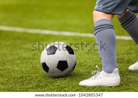 Football detail. Kicking the soccer ball. Football player feet and classic soccer ball on grass pitch.