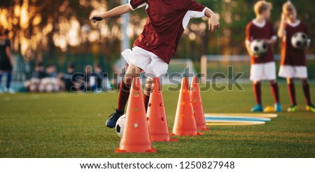 Football Drills: The Slalom Drill. Youth soccer practice drills. Young football players training on pitch. Soccer slalom cone drill. Boy in red soccer jersey shirt running with ball between cones