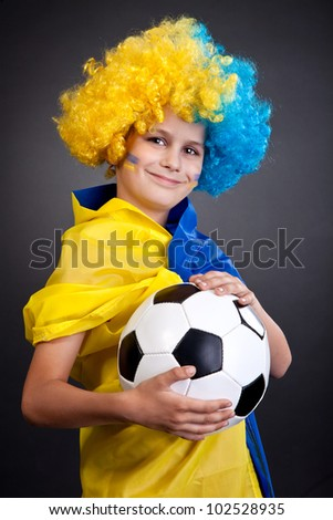 Football fan with a blue and yellow ukrainian flag painted on his face on black background