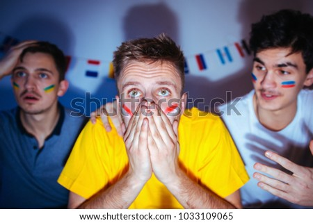 Football fans at home, watching the match, worried, praying for victory  #1033109065