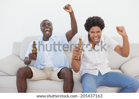 Football fans cheering holding beer bottles at home in the living room