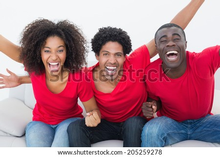 Football fans in red sitting on couch cheering at home in the living room