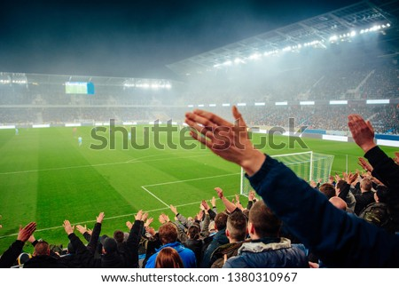 Football fans support the team at soccer Stadium #1380310967
