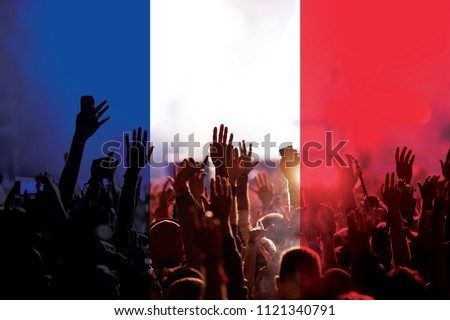 football fans supporting France - crowd in stadium with raised hands against french flag