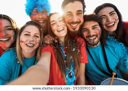 Football fans taking selfie during the soccer match event at stadium - Young people having fun supporting favorite club - Sport entertainment concept