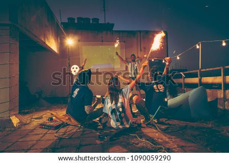 Football fans watching a game on a building rooftop, cheering for their team and waving with sparklers. Focus on the girl holding a sparkler #1090059290