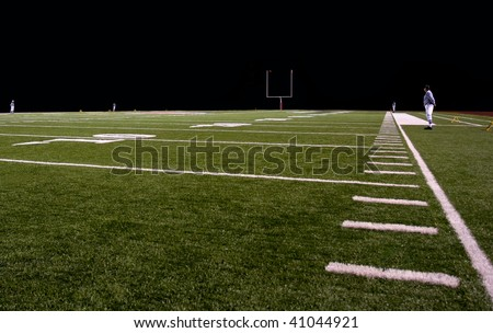 Football field at night with referees