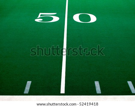 Football field with green turf and white yardlines and markers