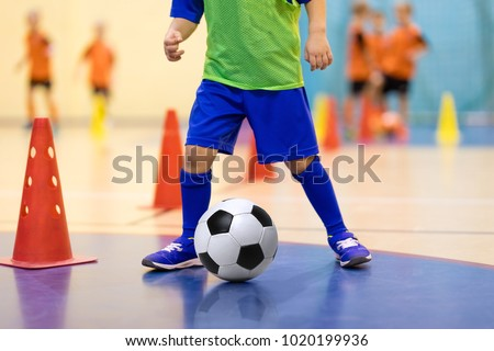 Football futsal training for children. Soccer training dribbling cone drill. Indoor soccer young player with a soccer ball in a sports hall. Player in blue uniform. Sport background. Stock photo ©
