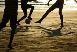 football game on the beach  against the sun