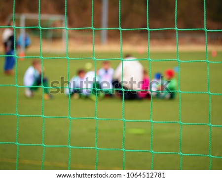 Football gate net. Soccer gate net. In blurry background stand players. Training of junior team.  #1064512781