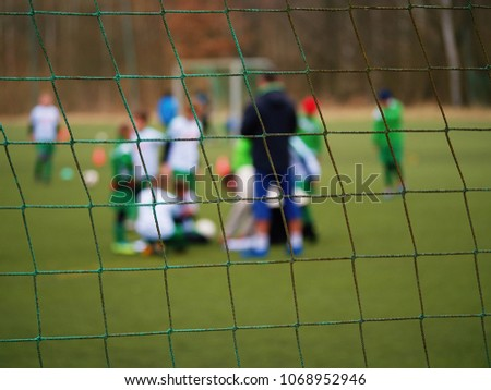 Football gate net. Soccer gate net. In blurry background stand players. Training of junior team.  #1068952946