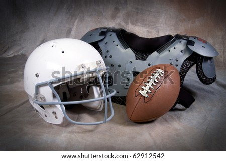 Football helmet and shoulder pads on tan background