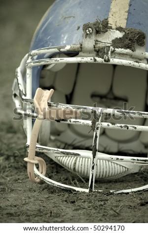 Football helmet covered with mud
