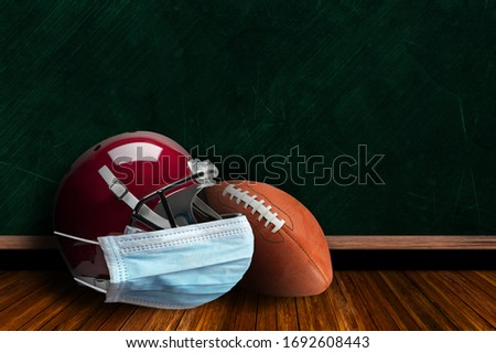 Football helmet wearing surgical mask on a background chalk board with copy space for text. Concept of COVID-19 coronavirus pandemic affecting American football season due to game or league suspension
