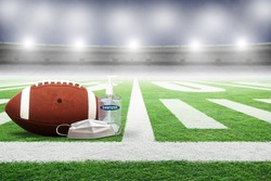 Football in empty stadium with hand sanitizer and medical face mask. Concept of football played without fans as part of social distancing to prevent spread of COVID-19 coronavirus in the New Normal.