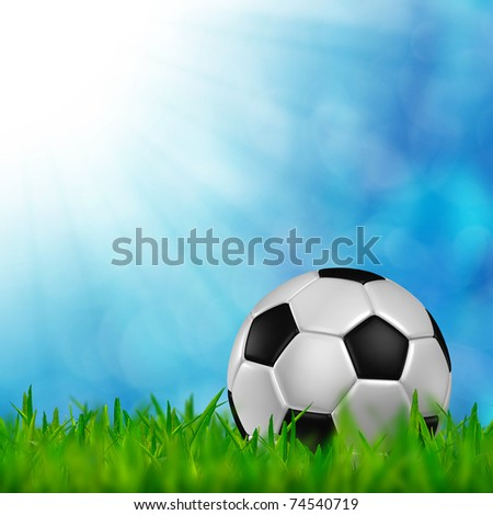 football in green grass over a blue sky