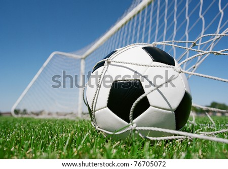 Football in the goal net against blue sky
