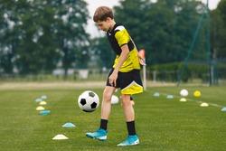 Football juggling. Teenage boy juggling soccer ball on a training pitch. Happy kid in jersey sportswear practicing soccer skills