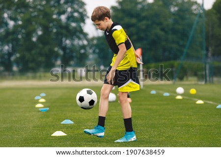 Football juggling. Teenage boy juggling soccer ball on a training pitch. Happy kid in jersey sportswear practicing soccer skills Foto stock ©