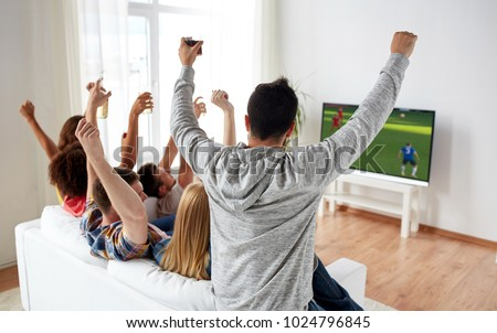 football, leisure and people concept - happy friends with drinks watching soccer game on tv at home and celebrating victory