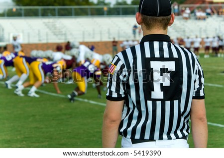Football official with black and white striped jersey, symbol is for field judge, at an american football game