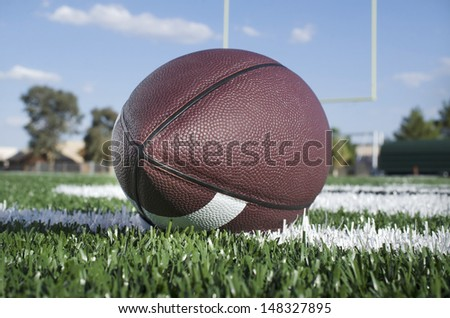 Football on field with goal post in background