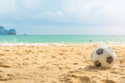football on the beach blue sky background