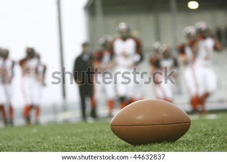 Football on the field with players in the background.