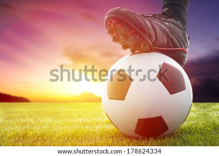 Shutterstock Football or soccer ball at the kickoff of a game with sunset
