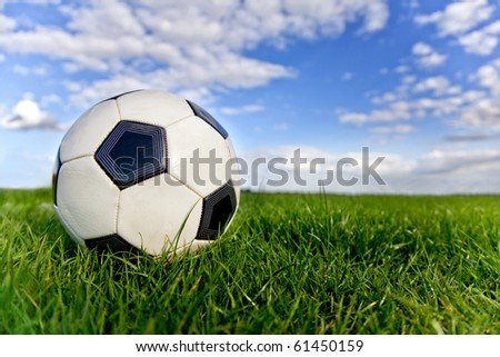 Football or soccer ball on a green lawn - outdoors