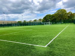 Football pitch and a cloudy sky. Green field. England.