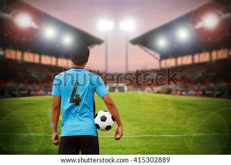 football player and soccer player holding ball on football stadium and stadium arena soccer field championship win for background,blurry and soft focus