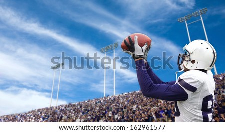 Football Player catching a Touchdown Pass