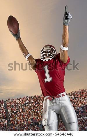 Football player celebrates after scoring a touchdown. Vertical shot.