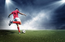 Football player, dark cloudy background. The imaginary stadium is modelled and rendered.