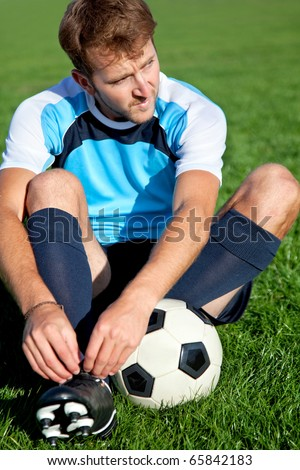 Football player getting ready for the game tying his shoes