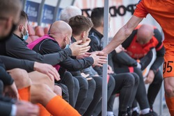 Football player gives five his college on the substitutes bench.